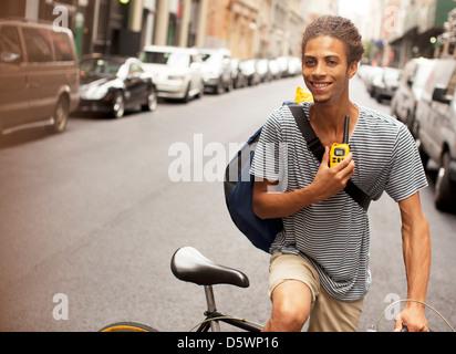 Man riding bicycle on city street - Stock Photo