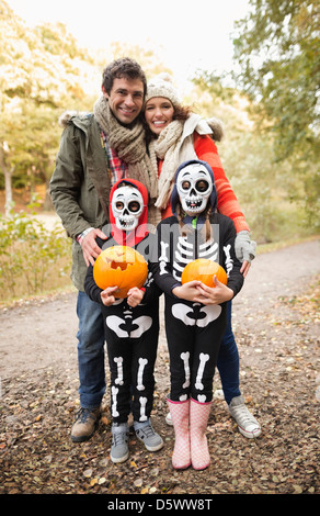 Parents smiling with children in skeleton costumes - Stock Photo