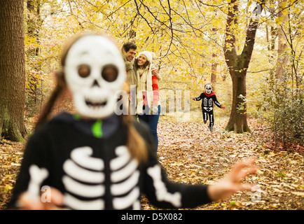 Children in skeleton costumes playing in park - Stock Photo