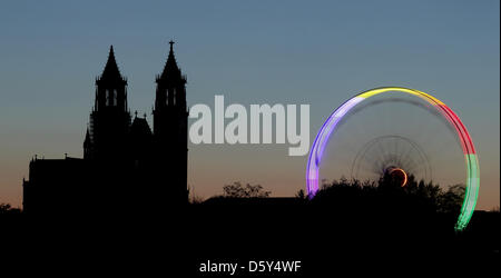 A ferris wheel, that is illuminated with colorfull lights, is visible in front of the Cathedral 'Saint Katharina - Stock Photo