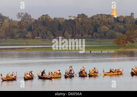 Tourist boats lining up on Taungthaman Lake, Myanmar, to view sunset over U Bein Teak Bridge 5 - Stock Photo