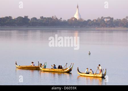Tourist boats lining up on Taungthaman Lake, Myanmar, to view sunset over U Bein Teak Bridge 3 - Stock Photo
