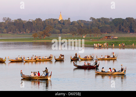 Tourist boats lining up on Taungthaman Lake, Myanmar, to view sunset over U Bein Teak Bridge 2 - Stock Photo