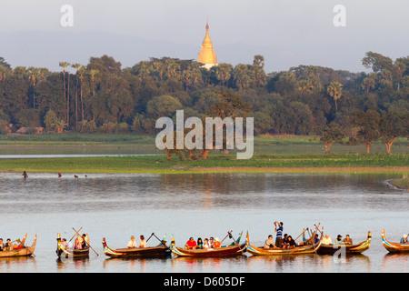 Tourist boats lining up on Taungthaman Lake, Myanmar, to view sunset over U Bein Teak Bridge 1 - Stock Photo