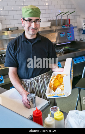 A man serving fish and chips in a traditional British fish and chip shop - Stock Photo