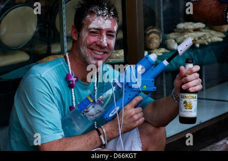 Bangkok, Thailand, April 13th, 2013. a tourist takes a beer brake during the water festival. Bangkok celebrates - Stock Photo