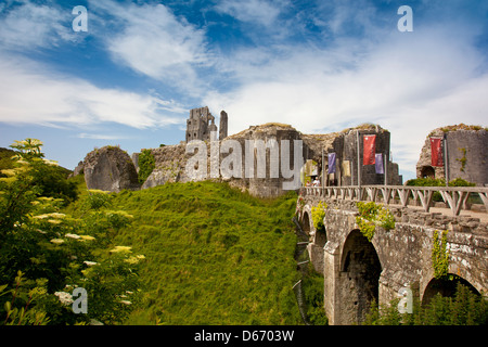 The entrance to the Castle ruins and bridge across the moat in Corfe Castle village, Dorset, England, UK - Stock Photo