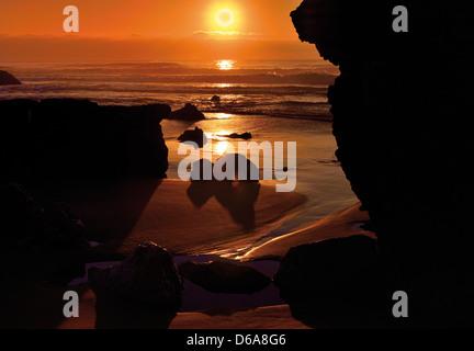 Portugal, Algarve: Sundown through the rocks at beach Praia do Tonel in Sagres - Stock Photo