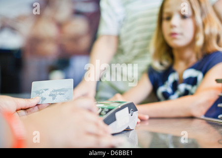 Cashier running credit card in store - Stock Photo