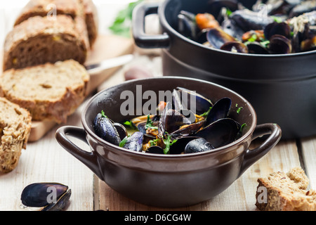 Mussels served in a sunny day with homemade bread - Stock Photo