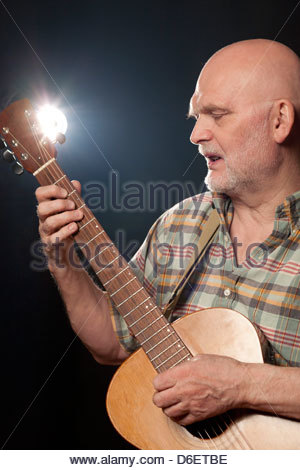 Senior Man playing acoustic Guitar Munich Germany - Stock Photo