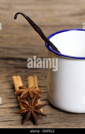 Cinnamon sticks, star anise and vanilla pod in an enamel cup on rustic wooden board - Stock Photo