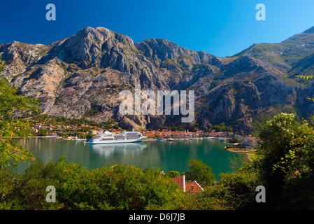 Cruise ship dwarfs the Old Town (Stari Grad), Kotor, Bay of Kotor, UNESCO World Heritage Site, Montenegro, Europe - Stock Photo