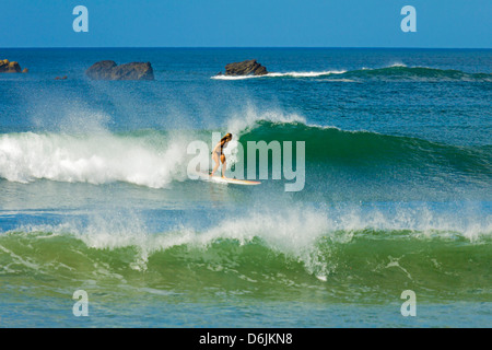 Girl surfing at Playa Guiones beach, Nosara, Nicoya Peninsula, Guanacaste Province, Costa Rica, Central America - Stock Photo