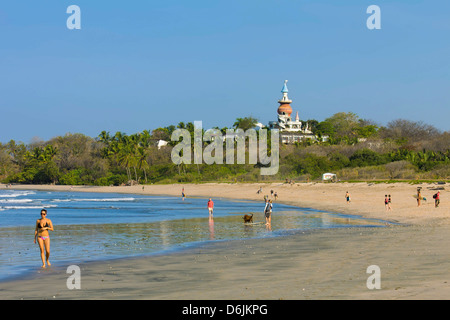 Walkers and the Nosara Beach Hotel at popular Playa Guiones beach, Nosara, Nicoya Peninsula, Guanacaste Province, - Stock Photo