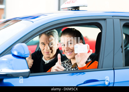 Driving School - Young woman steer a car, maybe she has a driving test, she holding proudly her driving license - Stock Photo