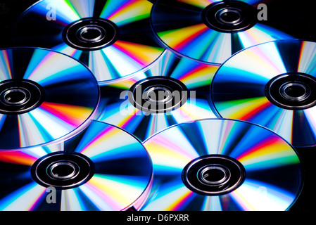 a collection of cd, dvd disks with rainbow colour reflections - Stock Photo