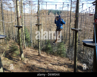 Teenage girl doing Go Ape in Dalby forest. - Stock Photo