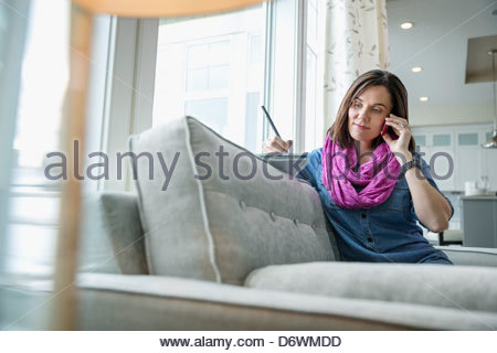 Mature woman answering phone call while writing in book at home - Stock Photo