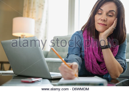 Mature woman with laptop writing in book at table - Stock Photo