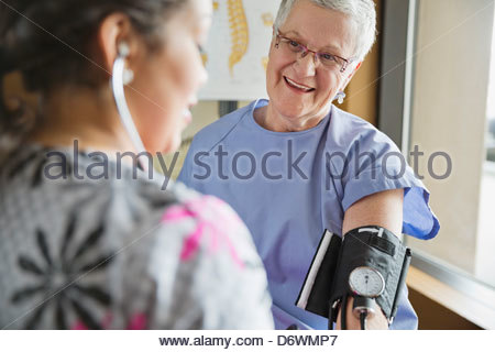 Young female nurse checking patient's blood pressure in clinic - Stock Photo