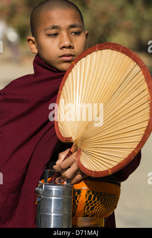 Novice monk with fan, lunchbox and collection bowl in Bagan, Myanmar - Stock Photo