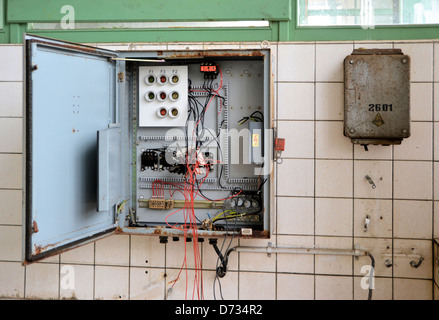 an old fuse box in a disused factory - Stock Photo