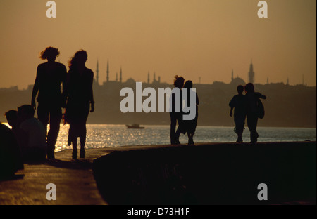 Couples walking along the seafront overlooking the Bosphorous Straits and the Golden Horn - Stock Photo