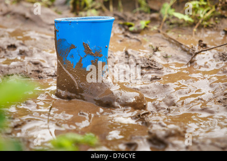 Children gumboot stuck in mud - Stock Photo