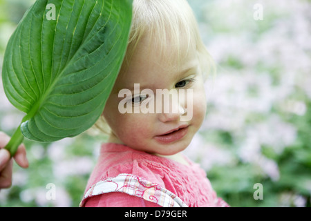 2 year old girl playing in garden. - Stock Photo