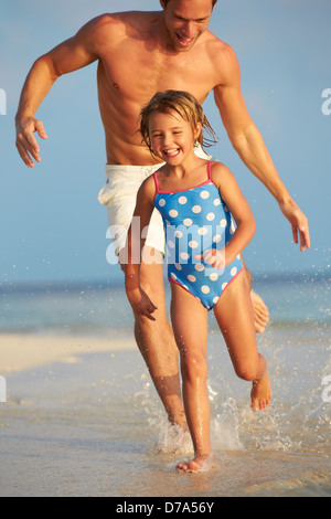 Father And Daughter Having Fun In Sea On Beach Holiday - Stock Photo