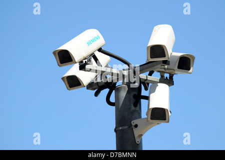 Several CCTV cameras bunched together with a blue sky background. - Stock Photo