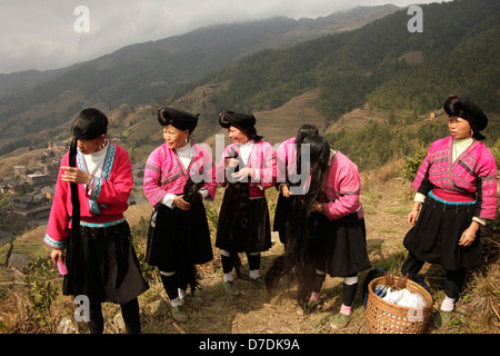 Women of the Yao minority with baskets, traditional costumes and their characteristic hairstyle at the village Ping - Stock Photo