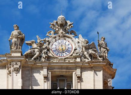 Clock with sculptures on facade of Saint Peter basilica. Vatican, Italy - Stock Photo