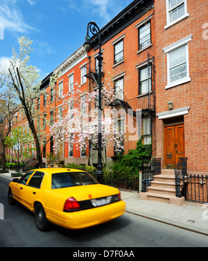 Yellowcab passes by Greenwich Village apartments in New York City. - Stock Photo