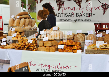 Two young women working on a stall selling home cooked bread and wares.           ( editorial use only) - Stock Photo