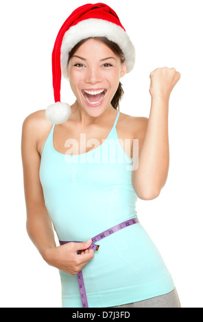 Christmas fitness woman excited about weight loss measuring waist with measuring tape wearing santa hat screaming - Stock Photo