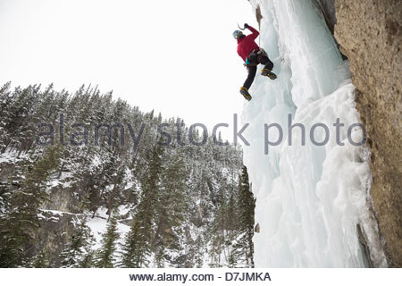 Low angle view of man climbing ice wall in mountains - Stock Photo