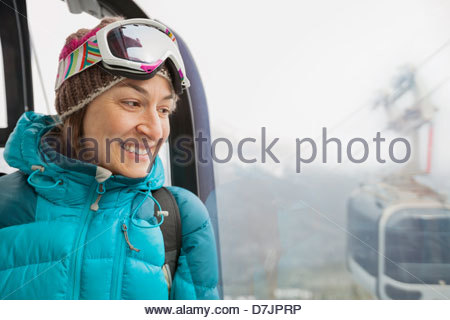 Smiling woman looking out gondola window - Stock Photo