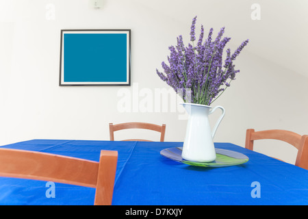 A vase of lavender on table with painting in background - Stock Photo