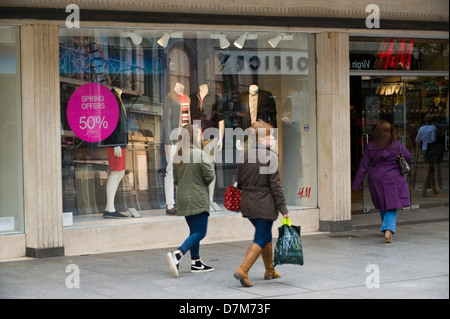 Shoppers walking past H&M store on busy high street in Exeter Devon England UK - Stock Photo