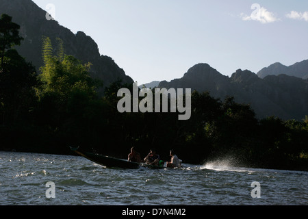 A local boat passes Vang Vieng on the Nam Song River. - Stock Photo