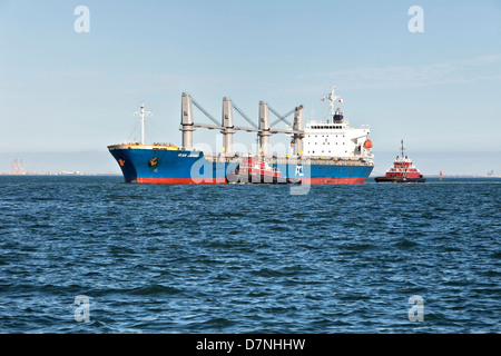 Harbor tugs assisting feighter transporting grain, entering Corpus Christi Deep Harbor. - Stock Photo