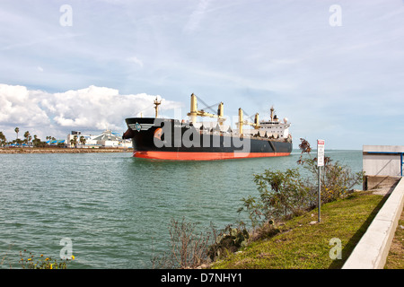 Freighter transporting grain, entering Port Of Corpus Christi. - Stock Photo