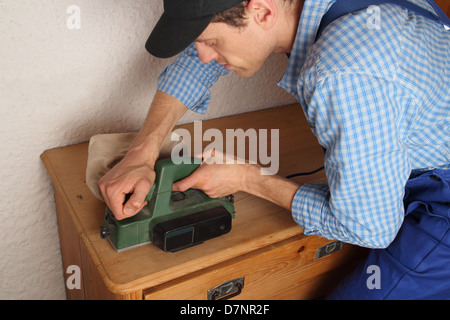 Carpenter renovating old furniture - Stock Photo