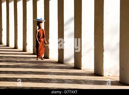 Novice Buddhist monk standing in the shadows of columns at Shwezigon Paya, Nyaung U, Bagan, Burma - Stock Photo