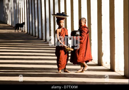 Novice Buddhist monks collecting alms, standing in the shadows of columns at Shwezigon Paya, Nyaung U, Bagan, Burma - Stock Photo