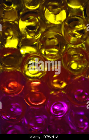 Various colors jelly balls in glass vase with back light. - Stock Photo