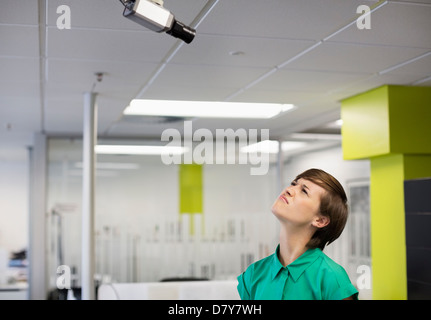 Businesswoman making faces at security camera - Stock Photo