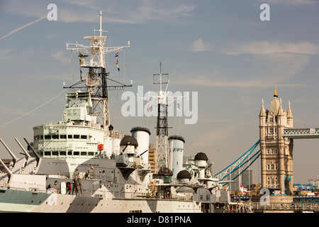 HMS Belfast moored on the River Thames in London and the Tower Bridge. - Stock Photo